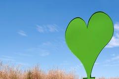 Zielony serce przeciw niebieskiemu niebu Fotografia Stock