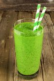 Zielony smoothie na nieociosanym drewnianym tle Fotografia Stock