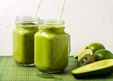 Zielony smoothie na zielonym tle robić avocado, cytryną i kiwi, obraz stock