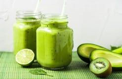 Zielony smoothie na zielonym tle robić avocado, cytryną i kiwi, zdjęcia royalty free