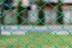 Zielony stalowego drutu łańcuszkowego połączenia sieci ogrodzenia fotografii zapas z ogrodowymi półdupkami Zdjęcie Royalty Free