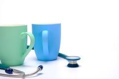 zielony stetoskop i dwa kawowego kubka Zdjęcia Stock