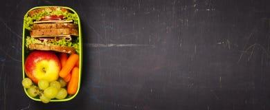 Zielony szkolnego lunchu pudełko z kanapką, jabłkiem, winogronem i marchewką, Fotografia Royalty Free