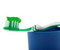 Zielony toothbrush z pasty lying on the beach na błękitnej plastikowej filiżance odizolowywającej nad białym tłem Obrazy Stock