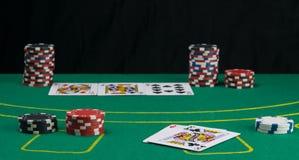 Zielony uprawia hazard stół z zakładać się układy scalonych i karty z tylnym czarnym tłem, fotografia stock
