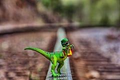 Zielony Velociraptor dinosaura odprowadzenie na sztachetowych torach szynowych obrazy royalty free