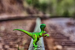 Zielony Velociraptor dinosaura odprowadzenie na sztachetowych torach szynowych zdjęcia stock