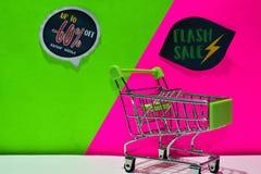 Zielony wózek na zakupy dołączający Do -60% i Błyskowego sprzedaż teksta na tle Daleko, Sklepowy Teraz zieleni i menchii zdjęcia stock