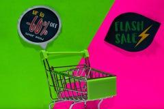 Zielony wózek na zakupy dołączający Do -60% i Błyskowego sprzedaż teksta na tle Daleko, Sklepowy Teraz zieleni i menchii zdjęcie royalty free