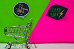 Zielony wózek na zakupy dołączający Do -60% i Błyskowego sprzedaż teksta na tle Daleko, Sklepowy Teraz zieleni i menchii obrazy stock