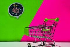 Zielony wózek na zakupy dołączający Do -60%, Sklepowego teksta na zieleni i menchii tła Daleko, Teraz zdjęcia royalty free