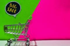 Zielony wózek na zakupy dołączający Duży sprzedaż tekst na zieleni i menchii tle fotografia royalty free