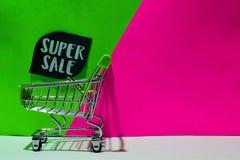 Zielony wózek na zakupy dołączający Super sprzedaż tekst na zieleni i menchii tle zdjęcia royalty free