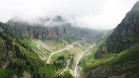Zielony wąwóz z rzeką Białe chmury zakrywają wierzchołki góry Zdjęcie Royalty Free