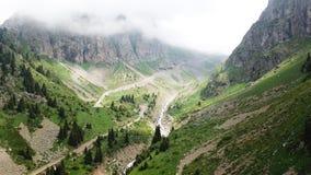 Zielony wąwóz z rzeką Białe chmury zakrywają wierzchołki góry Obraz Stock