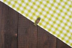 Zielony w kratkę tablecloth na drewnianym stole Zdjęcia Royalty Free