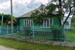 Zielony wiejski dom pod jabłonią z winnicą blisko metalu ogrodzenia zdjęcia stock