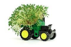 Zielony zabawkarski rolniczy ciągnik, zbierający, uprawiający ziemię maszynerię na białym tła miejscu dla teksta, odizolow obraz royalty free