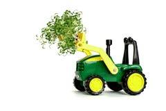 Zielony zabawkarski rolniczy ciągnik, zbierający, uprawiający ziemię maszynerię na białym tła miejscu dla teksta, odizolow obrazy royalty free