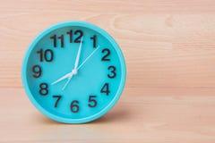 Zielony zegar na drewnianym tle, zegar mówić czas Tworzy śliwki Obraz Stock