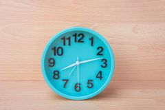 Zielony zegar na drewnianym tle, zegar mówić czas Tworzy śliwki Fotografia Royalty Free