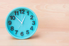 Zielony zegar na drewnianym tle, zegar mówić czas Tworzy śliwki Zdjęcia Stock