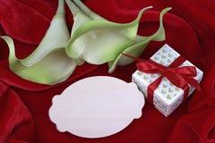 Zielonych i żółtych kalii lelui kwiatów prezenta zielony pudełko z czerwonym faborkiem na czerwonej tkaniny tła karcie dla teksta Obrazy Royalty Free