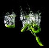 Zielonych pieprzy wody pluśnięcia czerni tło Obraz Stock