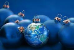 Ziemska kula ziemska jako boże narodzenia balowi między błękitnymi baubles, metafora uni Obrazy Royalty Free