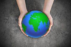 Ziemska planeta w żeńskich rękach Fotografia Stock