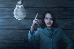 Ziemski godzina znak z azjatykcią biznesową kobietą daleko i żarówek światłami zdjęcia stock