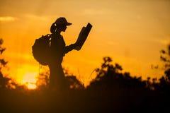 Zien de dragende reizigers van het silhouetmeisje wanneer het naderen van de zon, stock foto's