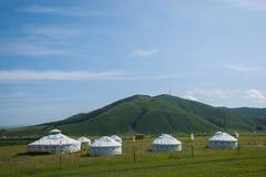 Zieren Sie und die Stadt von Flussuferwiese yurt stockfotos