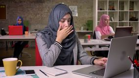 Ziewać zmęczonej pięknej arabskiej dziewczyny używa jej laptop przy desktop podczas gdy siedzący, koledzy na tle, nowożytne damy