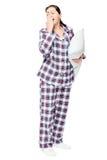 Ziewająca śpiąca kobieta w ciepłych piżamach trzyma gotową poduszkę na bielu obraz stock