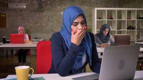 Ziewająca arabska kobieta w zmroku - błękitny hijab pracuje na jej laptopie podczas gdy inny biurowy kobiety ias obsiadanie za, s