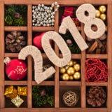 Ziffer 2018 auf dem Kasten mit Satz Weihnachtsdekorationen Stockfoto