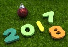 Ziffer 2018 auf grünem Gras mit rotem Weihnachtsball Stockfoto