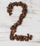 Ziffer von den Körnern des Kaffees auf einem hellen hölzernen Hintergrund Selektiver Fokus Lizenzfreies Stockbild