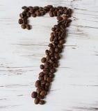Ziffer von den Körnern des Kaffees auf einem hellen hölzernen Hintergrund Selektiver Fokus Lizenzfreie Stockbilder