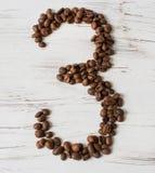 Ziffer von den Körnern des Kaffees auf einem hellen hölzernen Hintergrund Selektiver Fokus Stockbilder