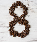 Ziffer von den Körnern des Kaffees auf einem hellen hölzernen Hintergrund Selektiver Fokus Lizenzfreie Stockfotografie