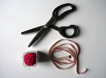 Zig Zag Scissors, tape measure and sewing pins royalty free stock image