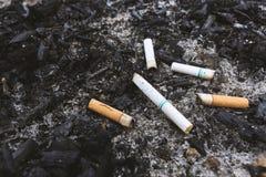 Zigarette auf der Asche mit Weichzeichnung im Hintergrund über L Lizenzfreie Stockfotos