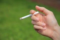 Zigarette in der Hand Stockbild