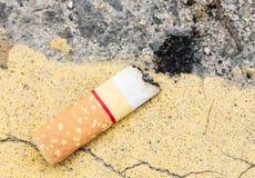 Zigarette und Asche auf Boden Stockfotografie