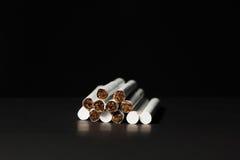 Zigaretten auf einem schwarzen Hintergrund Lizenzfreie Stockfotos