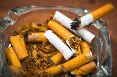 Zigaretten und Tabak, die innerhalb und um des Glasaschenbechers auf der Holzoberfläche, gesehen von oben, Antirauchenkonzept lie Stockfoto