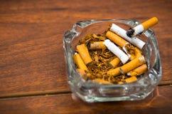 Zigaretten und Tabak, die innerhalb und um des Glasaschenbechers auf der Holzoberfläche, gesehen von oben, Antirauchenkonzept lie Lizenzfreie Stockfotos