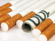 Zigaretten und teure Gewohnheit des Geldes Lizenzfreie Stockfotografie